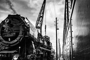 Stomende trein met oude wagon staat kolen te laden op station