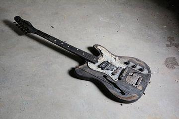 oude verbrande gitaar op de vloer van een ruïne van Heiko Kueverling