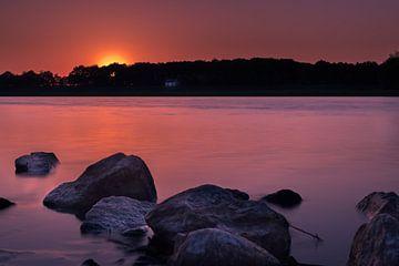 Bunter Sonnenuntergang auf der Maas mit Steinen im Vordergrund von Kim Bellen