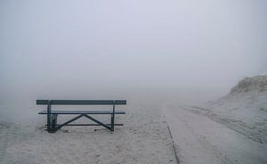 Verlaten bankje in de mist op het strand van Ameland. van