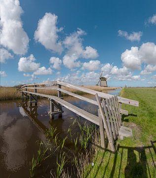 Fußgängerbrücke über einen Kanal mit Windmühlen, 't Zand, Noord-Holland, Niederlande von Rene van der Meer