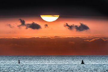 Zonsondergang boven het Wad met een wolkenband. van