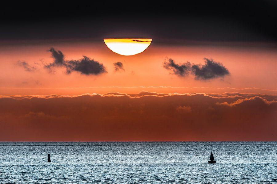 Zonsondergang boven het Wad met een wolkenband.
