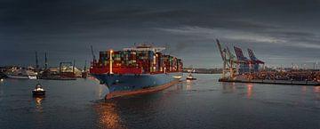 Groot containerschip bij een terminal in de vroege avonduren