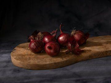 Stilleven van rode uien op een houten plank met een donkere achtergrond van Wendy Verlaan
