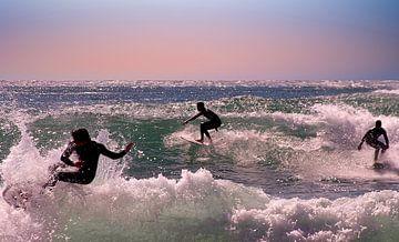Drie surfers op de golven van de Noordzee bij zonsondergang van Nisangha Masselink