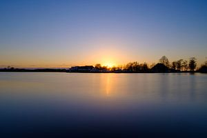 Ondergaande zon bij een meer, uitzicht op boten en huisjes. van Lidewij Olive
