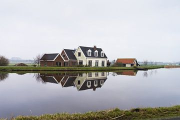 Boerderij aan de rand van water met reflectie in de buurt van Amsterdam, Nederland van Leoniek van der Vliet