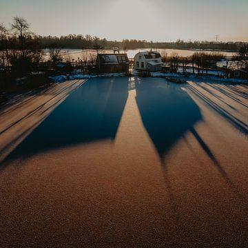 Schatig land huisjes in de zonsopkomst, schaduw valt op het ijs van Mike Helsloot
