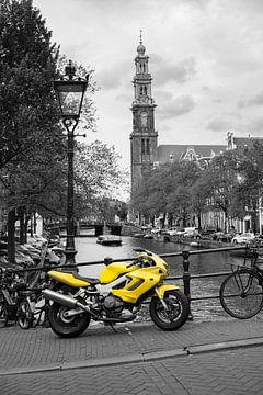 Gelbes Motorrad und Fahrräder parkten neben einem Kanal in Amsterdam von