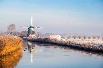 Hollandse molen in winters landschap aan het water van Inge van den Brande
