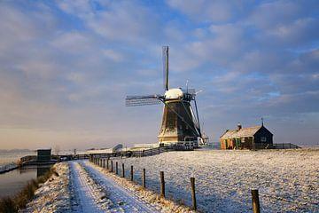 Mühle im warmen Sonnenlicht eines Wintersonnenaufgangs