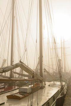 Oude traditionele zeilschepen afgemeerd tijdens een mistige ochtend van Sjoerd van der Wal