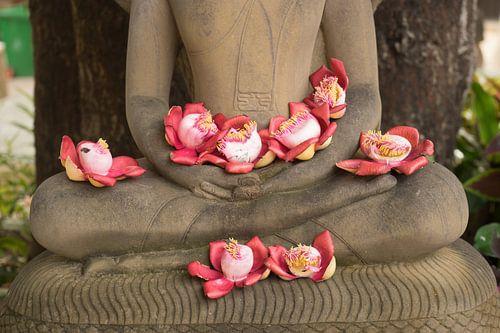 Bloemen op schoot bij Boeddhabeeld van