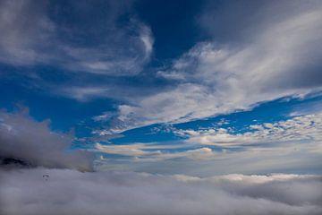 Champ de nuages blancs en bas, au-dessus du ciel bleu, à gauche un petit parapente vole, liberté...  sur Michael Semenov