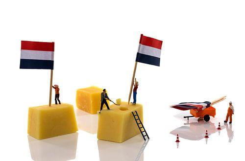 miniatuur poppetjes zetten vlag op de kaas