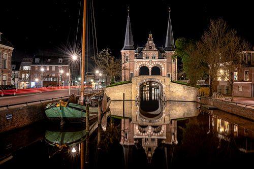 Spiegelend Sneker skûtsje en waterpoort in stadsgracht van Sneek
