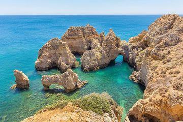 Felsen im blauen Meer auf der Küste in der Algarve Portugal von Ben Schonewille