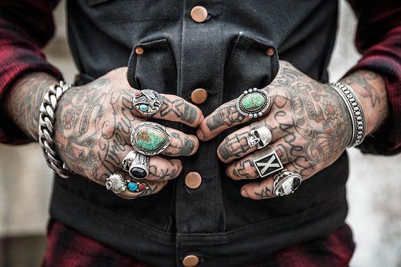 Man met getatoeëerde handen