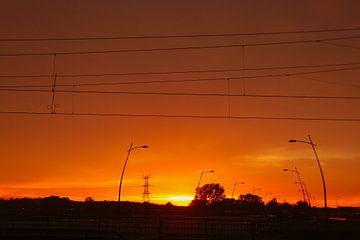 Zonsondergang boven de weg en spoorlijn van Vincent van der Tuin