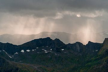 Lichtstralen door de regen over de bergen van Axel Weidner