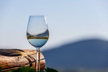 Verre à vin rempli à côté d'une poutre en bois sur Reiner Conrad
