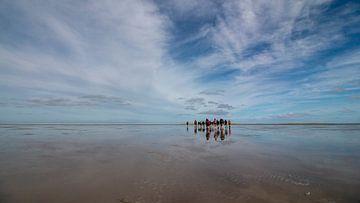 Auf einer unbewohnten Insel laufen Wanderer über das Land, das noch von der schwindenden Flut nass i von Studio de Waay