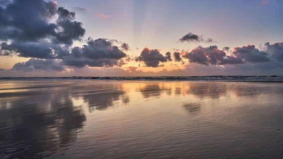Het strand en de reflectie van de wolken