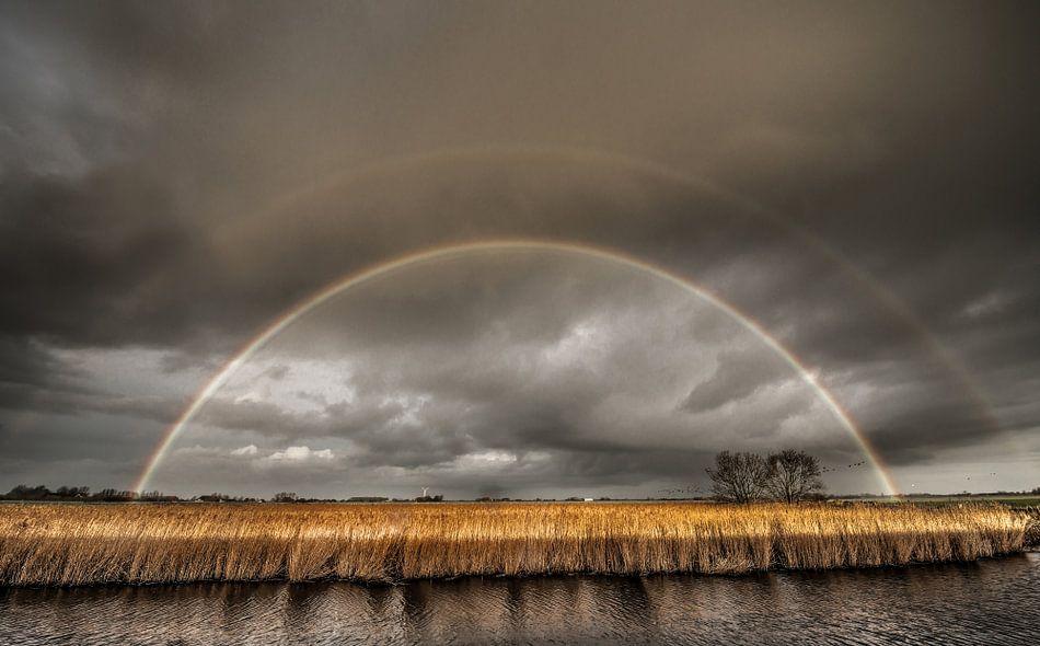 Regenboog achter IJsselmeerdijk