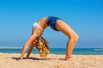 Jonge Nederlandse vrouw in bikini buigt achterover bij yoga op strand van Hurghada in Egypte van Ben Schonewille