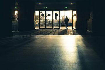 Wanderlaar in het centraal station van Amsterdam tijdens de zonsongergang.