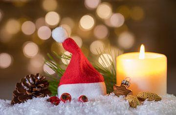 Kerst- of adventsdecoratie met brandende kaars en rode kerstmuts op sneeuw van Alex Winter