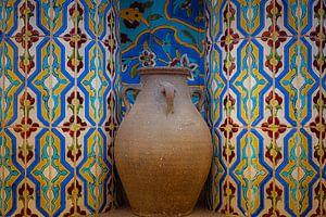 Kruik van aardewerk in nis met mozaiek tegeltjes