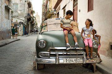 Kinderen spelen op een Cubaanse auto van Paula Romein
