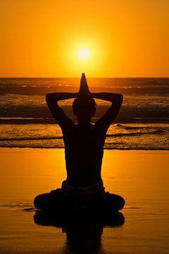 Yoga op het strand bij zonsondergang van Nisangha Masselink