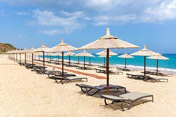 Strohsonnenschirme für Schatten in einer Reihe an der Küste von Kefalonia in Griechenland von Ben Schonewille