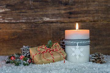 Brandende kaars met kerstgeschenk en decoratie van Alex Winter