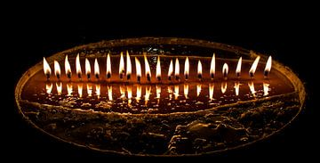 Brennen Butter Kerzen in einem dunklen Tempel in Tibet von Rietje Bulthuis