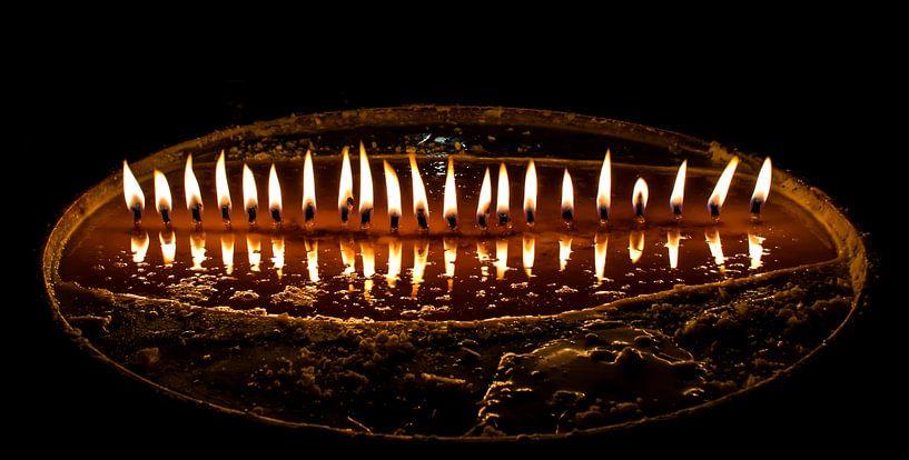 Brandende boterkaarsjes in een donkere tempel in Tibet van Rietje Bulthuis