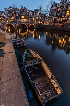 De avond valt. Een sloep dobbert in de Amsterdamse grachten. van Claudio Duarte
