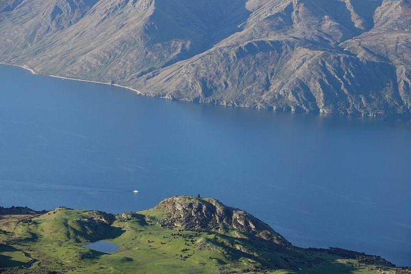 Kleine boot tussen hoge bergwanden op Lake Wanaka in Nieuw Zeeland van Aagje de Jong