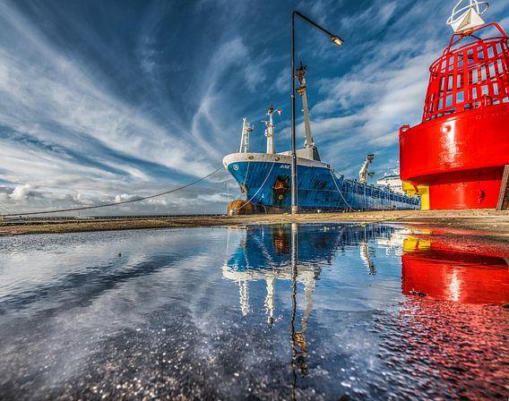 De haven van Harlingen, Friesland, met weerspiegeling in een plas.