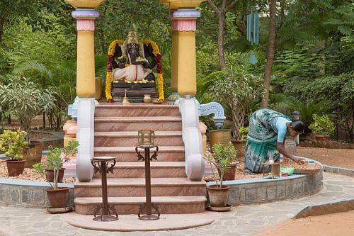 Indiase bezemende vrouw bij standbeeld van Ganesha van