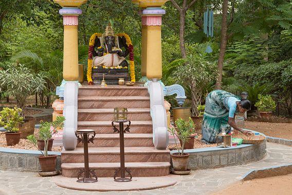 Indiase bezemende vrouw bij standbeeld van Ganesha