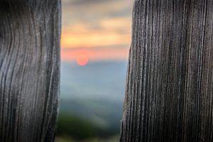 Zonsondergang achter een hek van