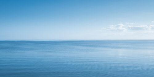 Een eindeloos Hollands waterlandschap met een wolk aan de horizon