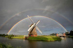 grote dubbele regenboog boven Nederlandse windmolen in zomerregen