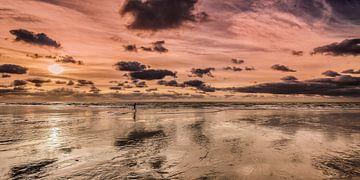 Eenzame renner op een leeg strand bij zonsondergang van Harrie Muis