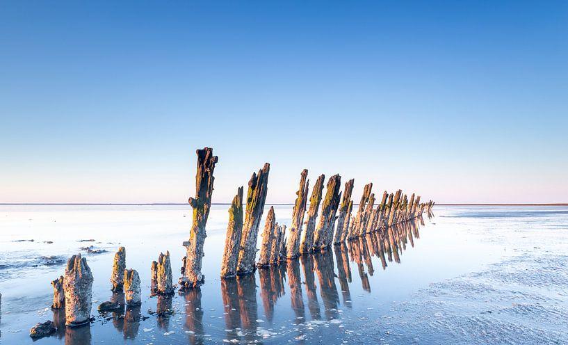 Reflectie van de paaltjes op de Waddenzee nabij Moddergat van Martijn van Dellen