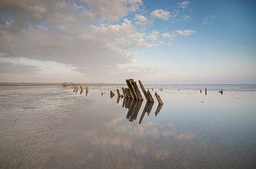 Prachtige weerspiegeling van houten paaltjes in zee van Patrick Verhoef